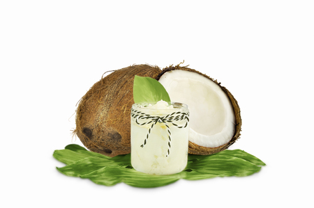 Jar of coconut oil and fresh coconuts isolated on white background. Stock Photo