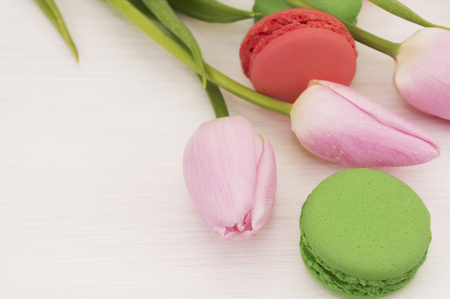 background with pink tulips and macaroons. Bouquet of tulips on white wooden table. Tulips with copy space for text. Stock Photo