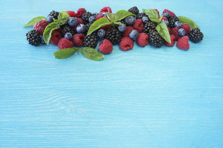 Various fresh summer berries on wooden background. Ripe raspberries, blackberries, blueberries and basil leaves. Berries at border of image with copy space for text.
