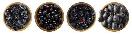 Black berries on a white background. Blackberries, blackcurrants, mulberries and grapes in a wooden bowl. Berry with copy space for text. Ripe and tasty black berries isolated on white. Top view.