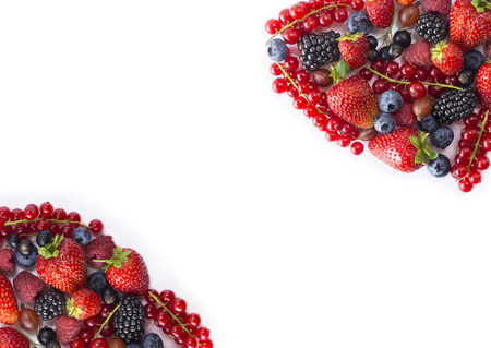 Black-blue and red food on white background. Ripe blueberries, red currants, raspberries, strawberries, gooseberries. Mixed berries with copy space for text. Various fresh summer berries on white background. Top view. Standard-Bild