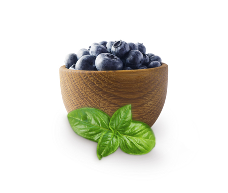 Blueberries in a wooden bowl isolated on white. Ripe blueberry with copy space for text. Blueberry with basil on a white background. Stock Photo