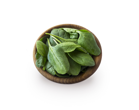 Spinach in wooden bowl. Top view. Spinach isolated on a white background. Green spinach with copy space for text.