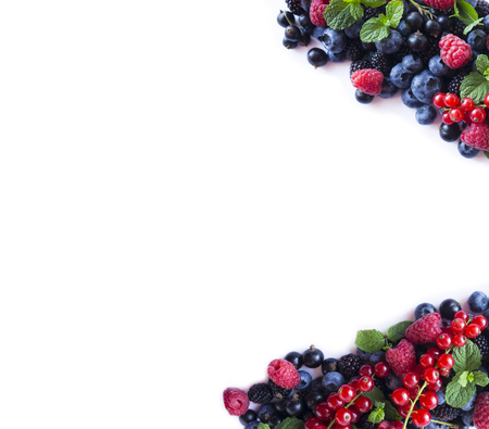 Mix berries and fruits at border of image with copy space for text. Ripe blueberries, blackberries, raspberries and currants  on white background. Top view. Black-blue and red food. Background berries. Various fresh summer berries.