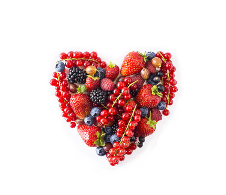 Heart shape assorted berry fruits on white background. Berries in heart shape isolated on a white. Ripe blueberries, red currants, raspberries, strawberries, gooseberries on a white background. Mixed berries with copy space for text. Various fresh summer berries on white background. Top view. Black-blue and red food. Standard-Bild