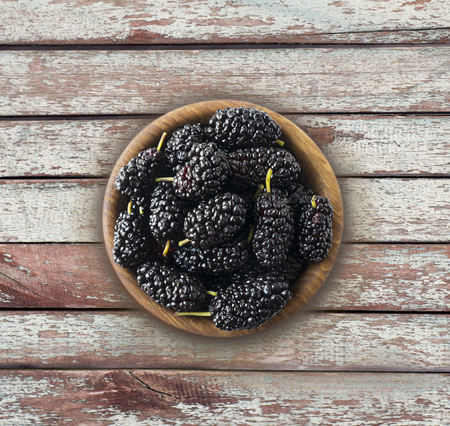 Mulberries in a wooden bowl with copy space for text. Ripe and tasty mulberry on a wooden background. Top view.