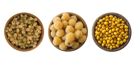 Yellow berries isolated on white background. Collage of different yellow berries. Yellow currants, yellow raspberries and sea buckthorn. Top view Stock Photo