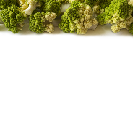 Roman cauliflower at border of image with copy space for text. Roman cauliflower on white background. Top view. Fractal texture of romanesco broccoli.