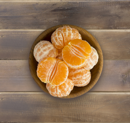 Top view. Fresh tangerines on a wooden background. Mandarins in a wooden bowl with copy space for text. Ripe and tasty tangerines. Clementines on a wooden table. Background tangerines.