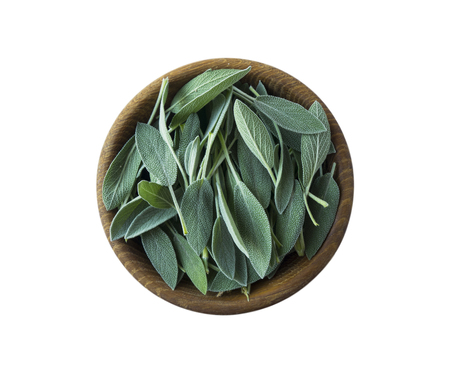Fresh sage leaves in wooden bowl isolated on white background. Top view. Salvia with copy space for text.