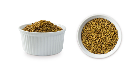 Fenugreek seeds in a wooden bowl isolated on white. Fenugreek seeds isolated on white background. Fenugreek with copy space for text.