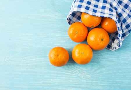 Top view. Fresh tangerines on a wooden background. Mandarins  with copy space for text. Ripe and tasty tangerines. Clementines on a wooden table. Background tangerines.