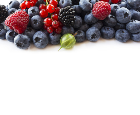 Mix berries on a white background. Ripe blueberries, red currants, backberries, gooseberries and raspberries on white background. Top view. Fruits and berries at border with copy space for text. Blue-black and red food.