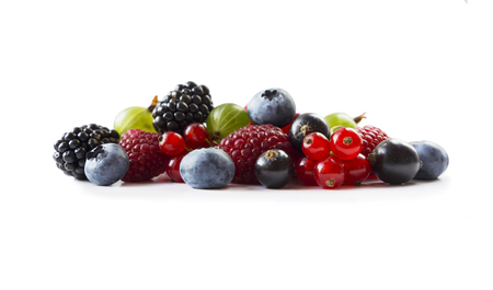 Berries isolated on white background. Ripe blueberries, blackberries, blackcurrants, raspberries, gooseberries and red currants. Mix fruits on white background. Mix berries with copy space for text. Various fresh summer berry. Black-blue and red berries on white. Imagens