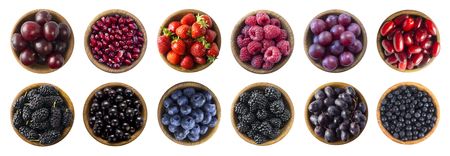 Red and black-blue food. Collage of different fruits and berries at green and red color. Raspberry, strawberry, currant, blueberry, plum, grape, pomegranate, mulberry, bilberry and blackberry. Top view. Berries and fruits isolated on white background.