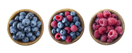 Ripe raspberries and blueberries on a wooden bowl. Raspberries and blueberries isolated on white background. Background of mix berries with copy space for text. Mix berries isolated on a white background. Various fresh summer.