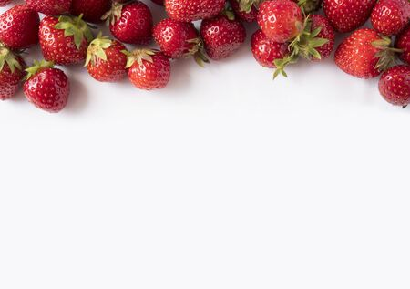 Strawberries on white background. Ripe berries close-up. Strawberries at border of image with copy space. Top view. Background of red berries. Background of fresh strawberries. Various fresh summer.