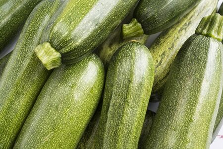 Green fresh zucchini stacked in a heap shot from above. Background of fresh zucchini. Top view.