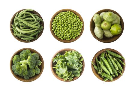 Fresh green vegetables isolated on a white background. Squash, green peas, broccoli, kale leaves and green bean in wooden bowl. Vegetables with copy space for text. Vegetables isolated on a white. Top