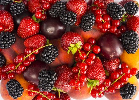 Mix berries and fruits on white background. Ripe blackberries, strawberries, red currants, plums and peaches. Top view. Background berries and fruits. Background of mix berries and fruits. Various fre 写真素材