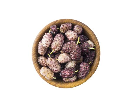 Mulberries on wooden bowl with copy space for text. Black and purple mulberry on white background. Ripe and tasty mulberry isolated on white background. Top view.