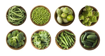 Vegetables isolated on a white. Squash, green peas, broccoli, kale leaves and green bean in wooden bowl. Vegetables with copy space for text. Top view. Studio photo. Fresh green vegetables isolated on 写真素材