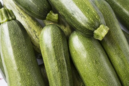 Background of fresh zucchini. Top view. Green fresh zucchini stacked in a heap shot from above. 写真素材