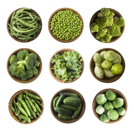 Vegetables isolated on a white. Squash, green peas, broccoli, kale leaves and green bean in wooden bowl. Vegetables with copy space for text. Top view. Studio photo. Fresh green vegetables isolated on a white background. Isolated macro food photo close up from above on white background.