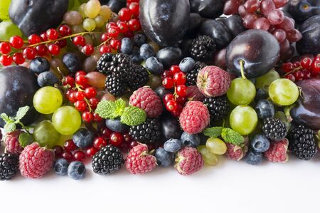 Ripe blackberries, blueberries, raspberries, red currants, plums and grapes. Mix berries and fruits. Top view. Background berries and fruits. Black-blue and red berries and fruits. Various fresh summer fruits.