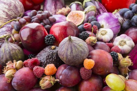 Background of fresh vegetables and fruits. Purple eggplant, plums, figs, apples, raspberries, avocado, grape, hazelnut, sweet pepper, tomato and garlic. Purple and red food. Different vegetables on the table.