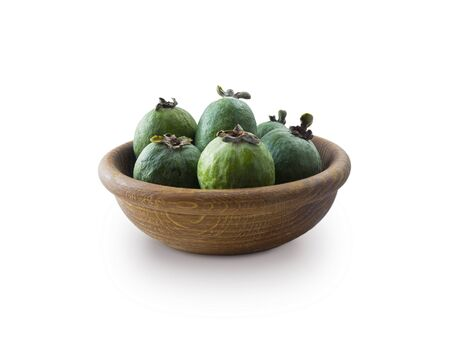 Green feijoa fruits in a wooden bowl isolated on white background.