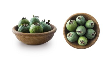 Green feijoa fruits in a wooden bowl isolated on white background. Top view. Fruits from different angles on white.