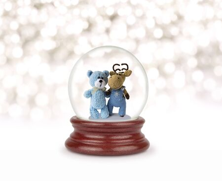 Christmas snow. Can be used as a Christmas or a New Year gift or symbol. Christmas and New Year design element. Toy glass snow globe with teddy bear and deer. Snow ball.