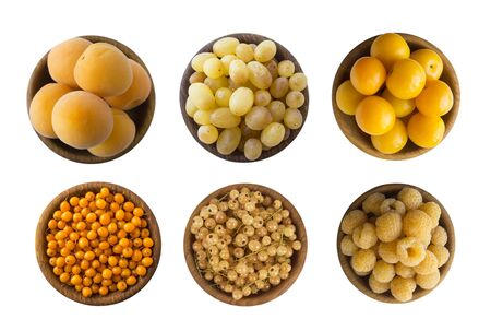 Yellow berriesfruits isolated on white background. Collage of different yellow berries. Yellow currants, yellow raspberries, grapes, apricots and plums. Top view. Fruits with copy space for text.
