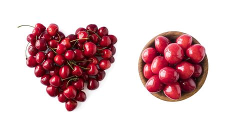 Heart shape red cherries on white background. Background made of cherry. Sweet cherry isolated on white background cutout. Various summer berries. Ripe cherries hill isolated on white. Top view. 스톡 콘텐츠