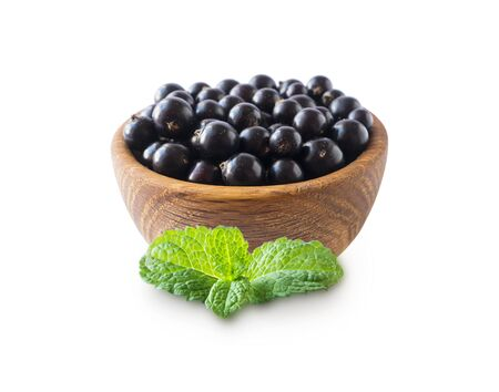 Black berries isolated. Blackcurrants in a wooden bowl isolated on white background. Blackcurrants with mint on white. Blackcurrants isolated on white background. Top view.