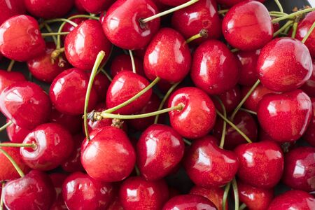 Fresh red cherries. Texture cherries fruits close up. Cherry fruit. Cherries with copy space for text. Top view. Background of cherries.