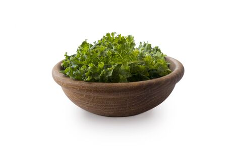 Kale leaves isolated on white background. Kale leaves with copy space for text. Kale in a wooden bowl on white background.