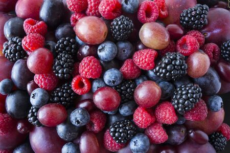 Background of fresh vegetables and fruits. Ripe blackberries, blueberries, plums, pink grapes, raspberries. Mix berries and fruits. Top view. Background berries and fruits. Various fresh summer fruits 스톡 콘텐츠