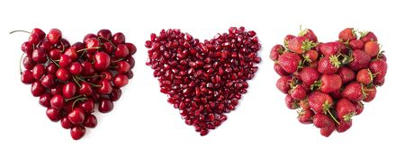 Heart shape red cherries, strawberries and pomegranate seeds  on white background. Background made of cherry, pomegranate and strawberry. Sweet fruits isolated on white background cutout.Top view. 스톡 콘텐츠