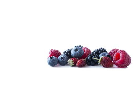 Berries isolated on white background. Ripe blueberries, blackberries, raspberries and wild strawberries. Background of mix berries with copy space for text. Mix berries on white background.