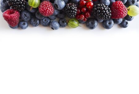 Mixed berries on a white background. Ripe blueberries, red currants, backberries, gooseberries and raspberries on white background. Top view. Fruits and berries at border with copy space for text. Blu