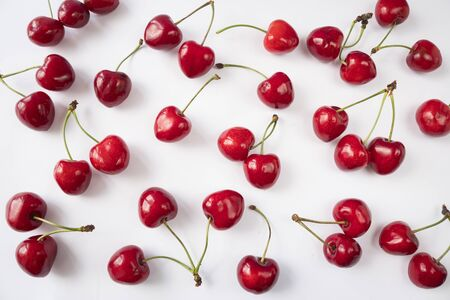 Fresh cherries scattered on white. Cherries on a white background. Cherry fruit. Creative fresh cherry pattern background with copy space. Top view. Sprinkled cherry on white background. Isolated frui 스톡 콘텐츠