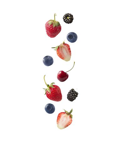 Isolated fresh berries float in the air. Falling blackberry, blueberry, cherry and strawberry fruits isolated on white background with clipping path. Mixed berries with a copy space for text.