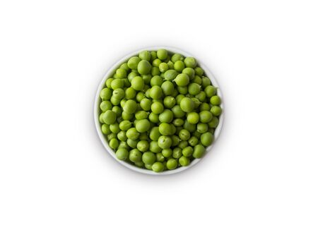 Green peas on bowl isolated on a white background. Vegetables with copy space for text. Green peas isolated on white. Top view. Isolated macro food photo close up from above on white background.