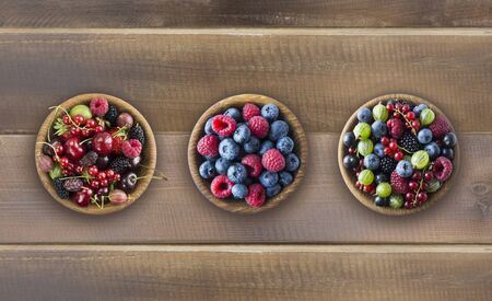 Top view. Fruits and berries in bowls on wooden background. Mixed fruits with copy space for text. Mixed berries on wooden background. Various fresh summer berries and fruits. Imagens