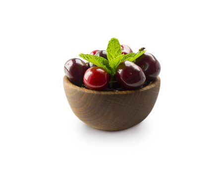 Red cherries in bowl isolated on white background. Ripe cherries and mint leaves close-up. Sweet and juicy berry with copy space for text. Various fresh summer fruits isolated on white.