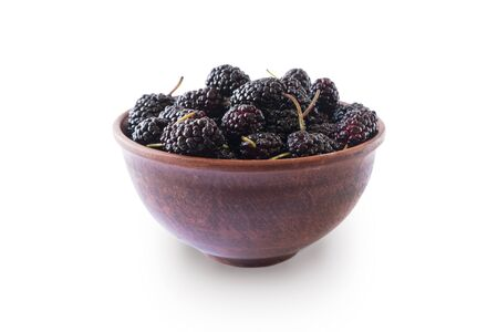 Mulberries in bowl isolated on white background. Black mulberry on white background. Ripe and tasty berry with copy space for text. Sweet and juicy mulberry isolated on white background.