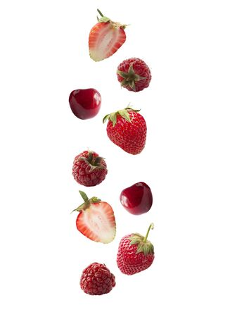 Isolated fresh berries float in the air. Falling strawberry, raspberry, cherry isolated on white background  . Mixed berries with a copy space for text. Collage of whole red berries.