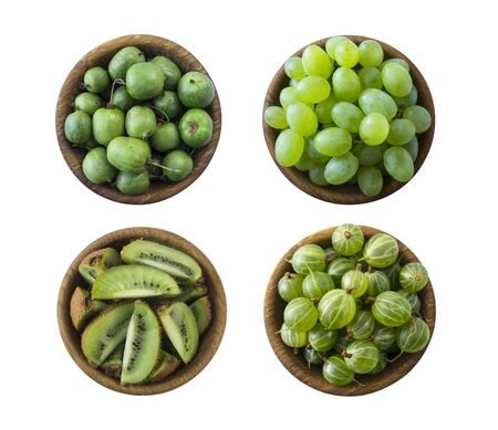 Green food isolated on a white background. Collage of different fruits and berries at green color.Green baby kiwi fruit actinidia, kiwi; gooseberry and green grapes in a wooden bowl. Fruit and berry. Imagens